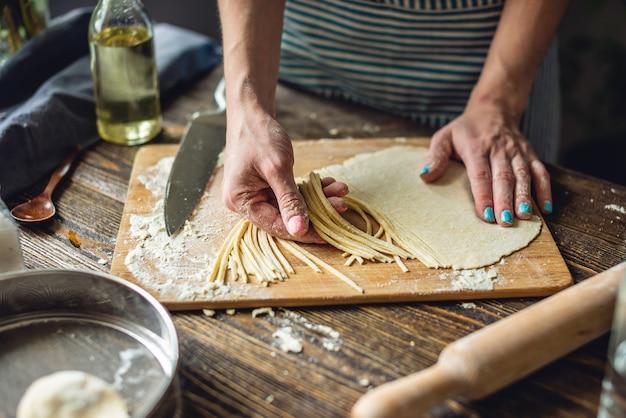 Una donna sta tagliando la pasta cruda con un coltello per fare le tagliatelle fatte in casa