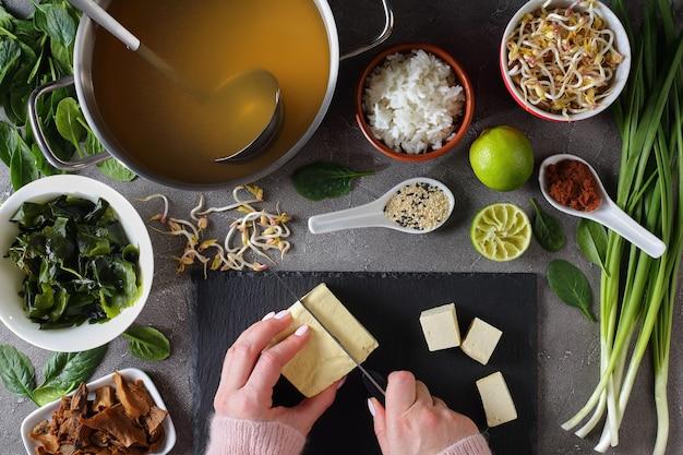 La donna sta tagliando il tofu a cubetti per la tradizionale zuppa di miso giapponese
