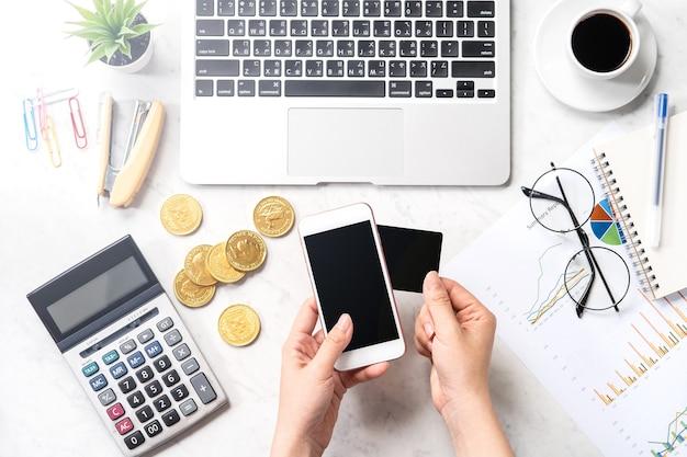 Una donna sta effettuando un pagamento online con carta e smartphone isolato su un moderno tavolo da ufficio in marmo