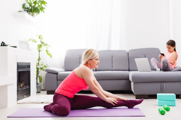 La donna sta facendo yoga online con il laptop durante l'autoisolamento nel suo soggiorno, nessun allenamento con l'attrezzatura, consigli di meditazione per i principianti. tempo in famiglia con i bambini, resta a casa.
