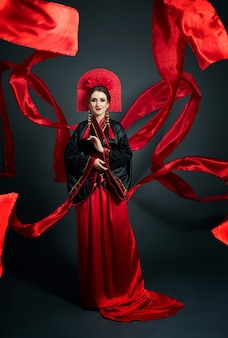 La donna è vestita con abiti popolari giapponesi cinesi rossi. tessuto volante, bellissimo ombrello e ventaglio in stile cinese giapponese, lunghi orecchini nelle orecchie. ragazza in posa su uno sfondo scuro