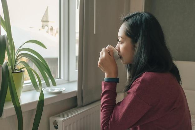 La donna sta bevendo il caffè vicino alle finestre per ammirare la vista sulla città.
