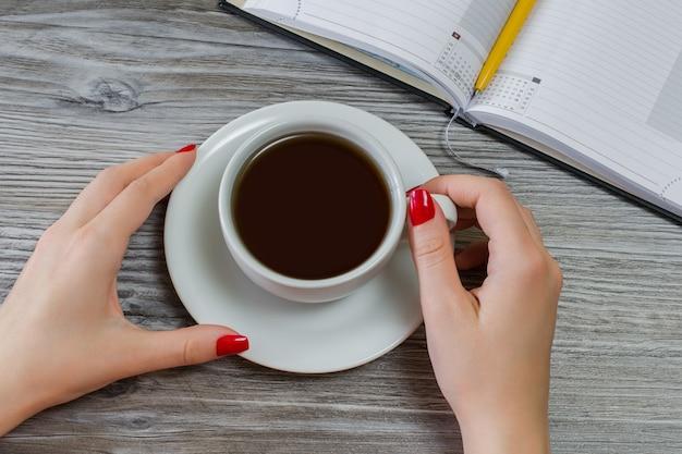 La donna sta bevendo il tè mentre ha del tempo libero dallo scrivere e dallo studio