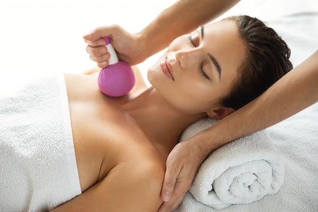 La donna sta godendo la terapia di massaggio asiatico con impacco alle erbe