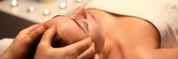 La donna riceve un massaggio facciale rigenerante in una stanza degli aromi
