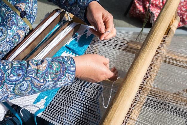 Una donna è tessuta a mano su un telaio a mano. il tessuto è fatto a mano.