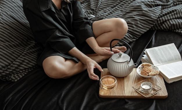 Una donna sta facendo colazione con tè e biscotti, sdraiata a letto in un giorno libero