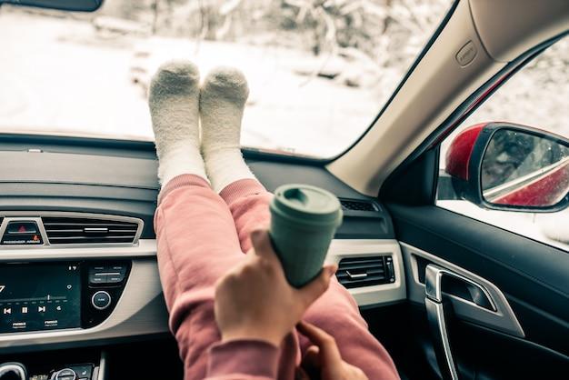 La donna sta tenendo la tazza di caffè all'interno dell'auto. stile di vita di viaggio. gambe sul cruscotto.