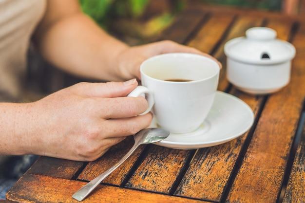 La donna sta tenendo una tazza di caffè in un caffè all'aperto