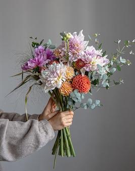 Una donna tiene in mano un bouquet festivo con fiori di crisatemo