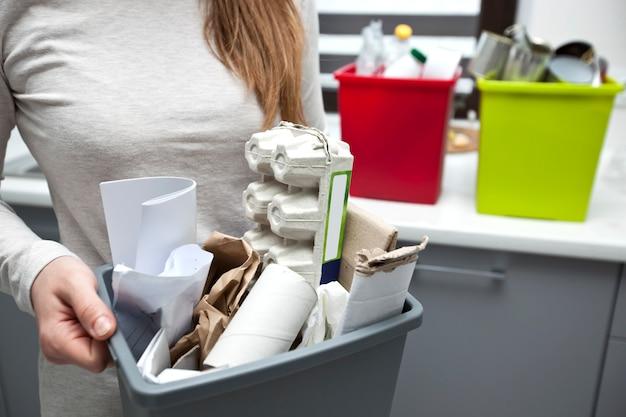 La donna tiene una scatola di plastica piena con immondizia di carta assortita