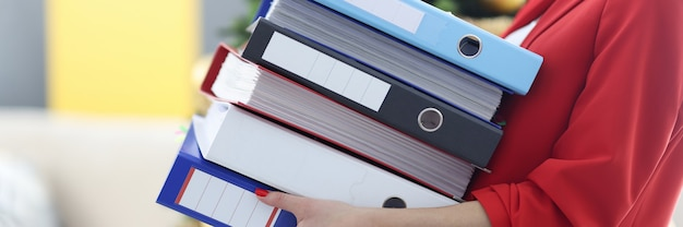 La donna sta tenendo una pesante pila di cartelle con i documenti. donne nel concetto di affari