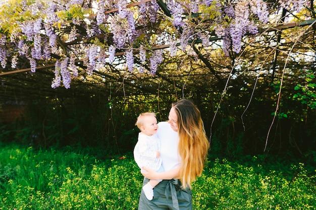 La donna sta tenendo il suo bambino sotto un albero di glicine