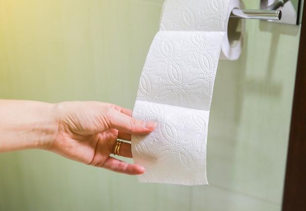 La donna tiene in mano la carta igienica.