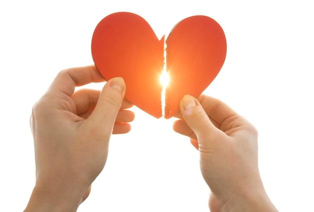 La donna tiene in mano due parti di cuore infranto davanti al cielo luminoso