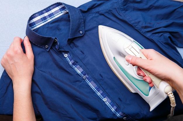 La donna sta stirando la camicia dell'uomo. vista dall'alto. concetto di lavoro domestico.