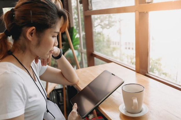 La donna sta guardando il tablet e bevendo caffè al bar