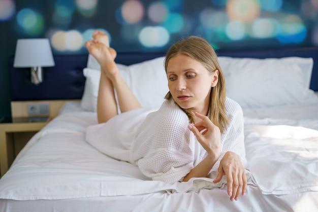 La donna giace in una vestaglia sul letto