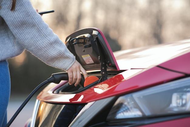 La donna sta tappando il veicolo elettrico per caricare la batteria dell'auto al parcheggio. avvicinamento. veicolo elettrico con cavo di ricarica collegato, parcheggio per veicoli elettrici, cavo per caricabatterie, stazione di ricarica, futuro sostenibile.