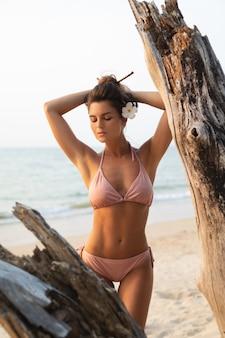 La donna sta proponendo accanto al legname galleggiante sulla spiaggia