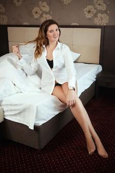 La donna è in posa in una camera d'albergo al mattino vicino al letto