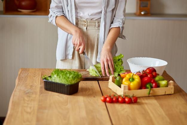 La donna sta preparando insalata di verdure in cucina, tagliando foglie di insalata su tagliere di legno, concetto di cibo sano, vegano o dieta.