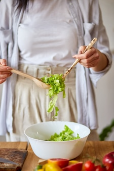 La donna sta preparando un'insalata di verdure in cucina, mescolando foglie di insalata e verdure in una ciotola bianca, concetto di cibo sano, vegano o dieta.