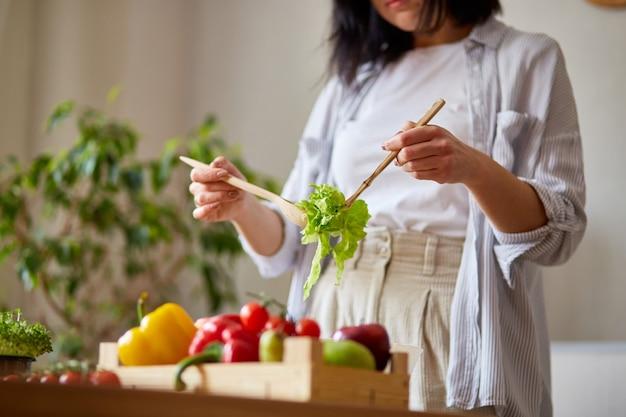 La donna sta preparando l'insalata di verdure in cucina