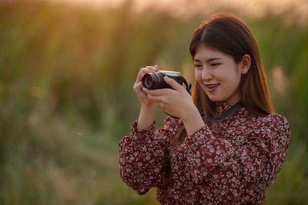 La donna è una fotografa professionista con fotocamera mirrorless nella foresta