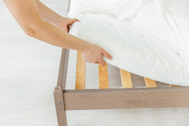 La donna sta mettendo il copriletto o il coprimaterasso sul letto o rimandando il processo di pulizia Foto Premium