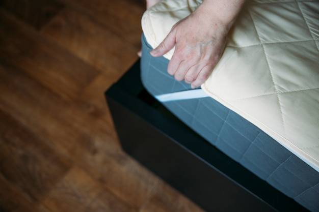 La donna sta mettendo il copriletto o il coprimaterasso sul letto o rimandando il processo di pulizia