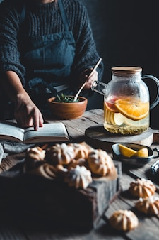 La donna sta leggendo e tè caldo con pompelmo fresco su tavoletta di legno. bevanda salutare, eco, vegana.