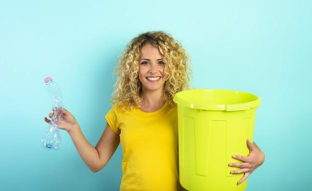 La donna è pronta a mettere una bottiglia di plastica nel bidone della spazzatura. sfondo ciano
