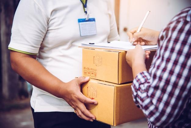 La donna riceve una cassetta dei pacchi dal personale addetto alle consegne.