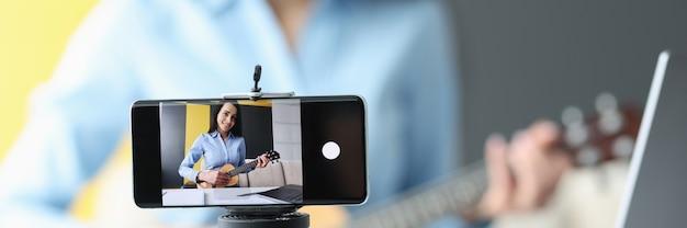 La donna sta registrando video sullo smartphone mentre suona la chitarra a corsi di formazione a distanza per musicisti