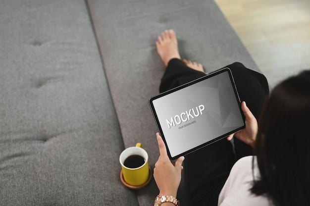La donna si sta rilassando con il tablet mentre è sdraiato sul divano nel soggiorno
