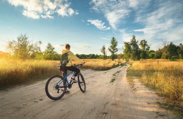 La donna sta guidando una mountain bike in una strada campestre al tramonto in estate. paesaggio colorato con ragazza sportiva con zaino in bicicletta, campo, strada sterrata, erba verde, cielo blu. sport e viaggi