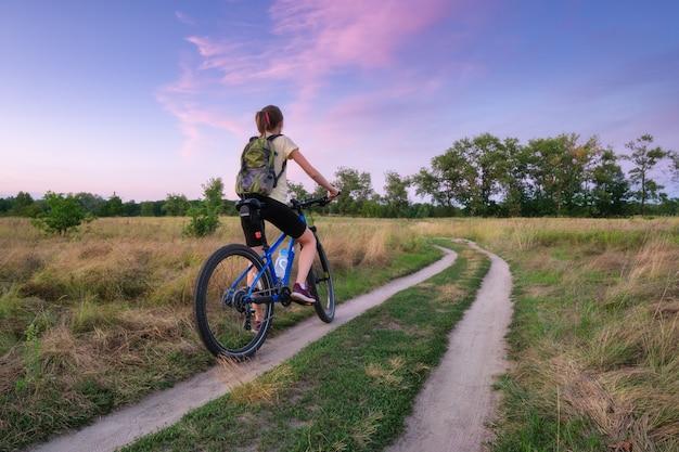 La donna sta guidando una mountain bike in una strada campestre al tramonto in estate. paesaggio colorato con ragazza sportiva con zaino in bicicletta, campo, strada sterrata, erba verde, cielo viola. sport e viaggi
