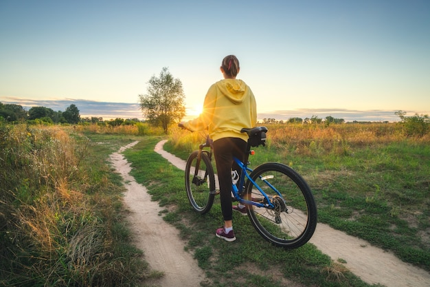 La donna sta guidando una mountain bike in una strada campestre al tramonto in estate. paesaggio colorato con ragazza sportiva in felpa gialla, bicicletta, campo, strada sterrata, erba verde, alberi, cielo. sport e viaggi