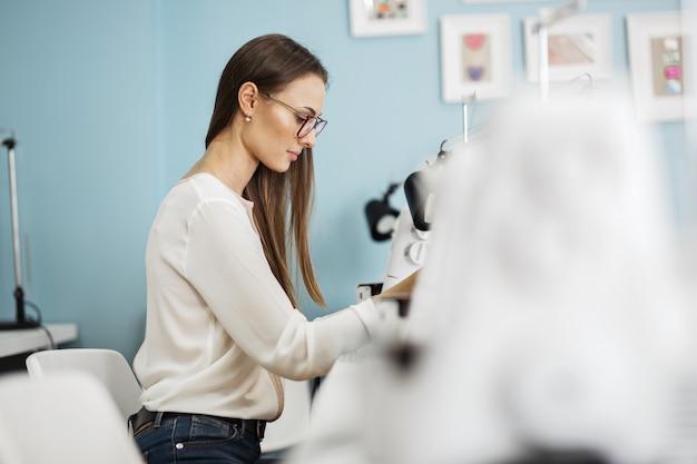 Una donna cuce con la macchina da cucire elettrica laboratorio sartoriale di moda
