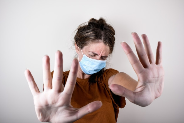 La donna è scioccata in una maschera medica e una maglietta marrone mostra un segnale di stop con le mani isolate. la donna incoraggia a rimanere a casa.