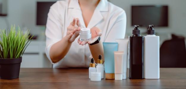 La donna sta mostrando il trucco sui prodotti cosmetici e video in diretta sulla fotocamera digitale digitale