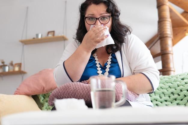 Una donna è malata seduta su un letto in una stanza