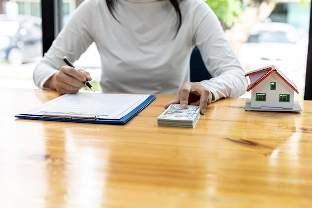 Una donna sta firmando un contratto per l'acquisto di una casa e depositando una certa somma sul progetto di costruzione di una casa, mette da parte una somma forfettaria per la caparra per l'acquisto della casa. idee di trading immobiliare.
