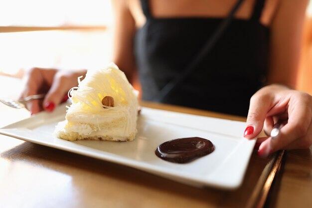 La donna è seduta al bar su un piatto di torta dolce con un delizioso concetto di torta al cioccolato liquido