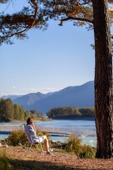 Una donna è seduta su una sedia pieghevole sulla riva di un fiume di montagna in una bella giornata calda sotto un grande albero. un luogo calmo e tranquillo per rilassarsi e riflettere. attrezzatura e riposo del turista.