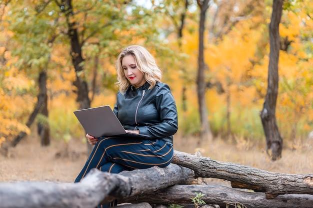 Una donna è seduta a un computer portatile nel parco su un tronco
