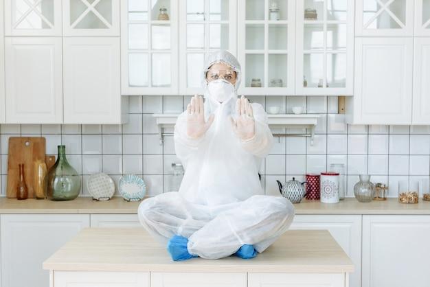 Una donna è seduta su un tavolo a casa in cucina mostrando un segnale di stop. indossare equipaggiamento protettivo. pandemia di covid-19
