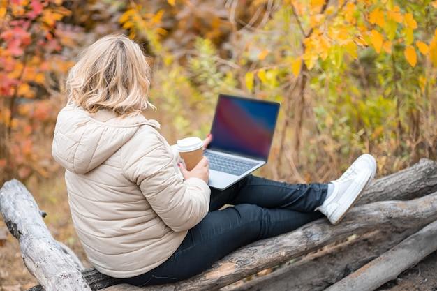 Una donna è seduta con la schiena e lavora a un laptop in un parco autunnale