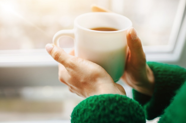 La donna è seduta su un davanzale in legno vicino alla finestra con una tazza di tè